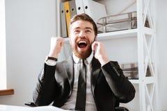 O homem de negócios feliz que fala pelo telefone e faz o gesto do vencedor imagem de stock