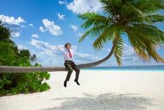 O homem de negócios feliz que senta-se na palma e relaxa Imagem de Stock