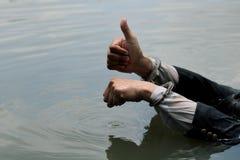 O homem de negócios foi prendido algemas e por afogamento foto de stock royalty free