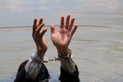 O homem de negócios foi prendido algemas e por afogamento imagens de stock royalty free