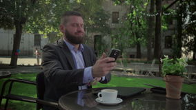 O homem de negócios furado fecha o portátil e o smatphone da consultação outdoor tiro do steadicam vídeos de arquivo