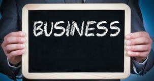 O homem de negócios guarda um quadro-negro com as mãos com plano de negócios redigido em um fundo azul ilustração royalty free