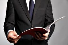 O homem de negócios guarda uma brochura Imagens de Stock