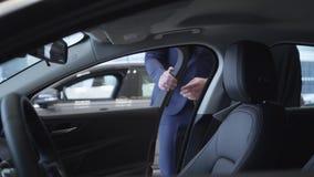 O homem de negócios irreconhecível em olhares do terno dentro do carro, a seguir abre a porta e a mulher bonita senta-se dentro d filme