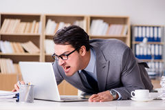 O homem de negócios irritado com demasiado trabalho no escritório foto de stock royalty free