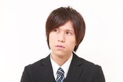 O homem de negócios japonês novo preocupa-se sobre algo Fotografia de Stock