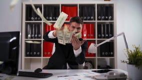 O homem de negócios joga acima dólares no escritório filme