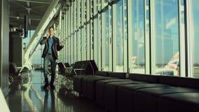 O homem de negócios jovem alegre está falando sobre um telefone celular no aeroporto filme