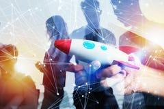 O homem de negócios lança sua empresa startup Hando que guarda um foguete de madeira exposição dobro com efeitos da rede imagem de stock royalty free