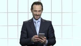 O homem de negócios maduro atrativo recebeu uma mensagem em seu telefone video estoque