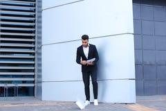O homem de negócios masculino árabe do homem recolhe papéis e originais perto do fotografia de stock