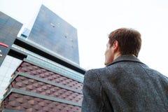O homem de negócios masculino novo está sonhando Vista da parte de trás do homem da parte inferior até o prédio de escritórios do imagem de stock