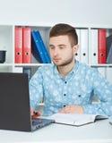 O homem de negócios masculino novo toma as notas que olham o portátil que senta-se no escritório Fotografia de Stock Royalty Free