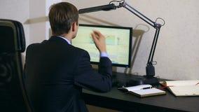 O homem de negócios monitora mudanças na programação na troca de moeda, olhando o monitor do computador vídeos de arquivo