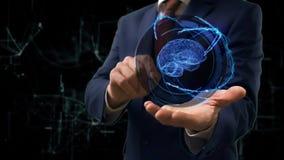 O homem de negócios mostra o cérebro do holograma 3d do conceito em sua mão