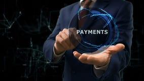 O homem de negócios mostra pagamentos do holograma do conceito em sua mão vídeos de arquivo