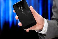 O homem de negócios mostra smartphone quebrado Fotos de Stock