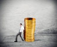 O homem de negócios move uma pilha das moedas conceito da dificuldade ao dinheiro de salvamento fotos de stock royalty free