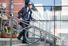 O homem de negócios na bicicleta levando do capacete de impacto pisa para baixo Imagens de Stock Royalty Free