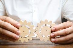 O homem de negócios na camisa branca conecta duas engrenagens de madeira Simbolismo de estabelecer processos de negócios e comuni imagem de stock