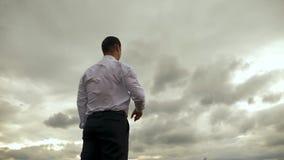 O homem de negócios na camisa branca está jogando com o avião de papel do voo contra o fundo de nuvens escuras Movimento lento vídeos de arquivo