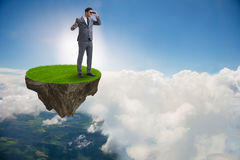 O homem de negócios na ilha do voo com binóculos Imagem de Stock Royalty Free