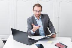 O homem de negócios na mesa de escritório gesticula com uma pena em seu ha imagens de stock
