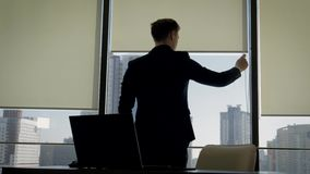 O homem de negócios na posição do escritório na janela e abre as cortinas para fazer mais brilhante filme