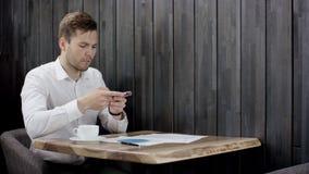 O homem de negócios na roupa do smat está fazendo a foto dos papéis no telefone celular e está enviando-os a alguém no café video estoque