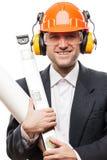 O homem de negócios no capacete do capacete de segurança da segurança que guarda os desenhos de papel planeia Fotografia de Stock