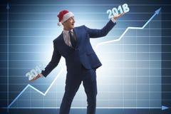 O homem de negócios no chapéu de Santa que guarda 2017 e 2018 Fotografia de Stock