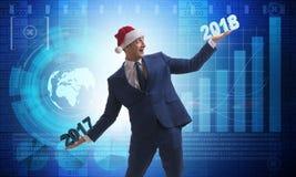 O homem de negócios no chapéu de Santa que guarda 2017 e 2018 Fotos de Stock