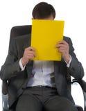 O homem de negócios no escritório senta-se em uma cadeira imagem de stock