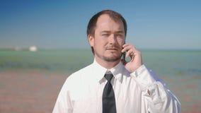 O homem de negócios no fundo do mar bonito que fala no telefone, resolvendo casos video estoque