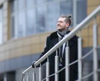 O homem de negócios no inverno reveste, estando perto do escritório imagem de stock