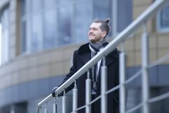 O homem de negócios no inverno reveste, estando perto do escritório foto de stock royalty free