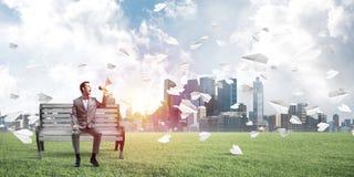 O homem de negócios no parque do verão que anuncia algo no altifalante e no papel aplana o voo ao redor Imagens de Stock