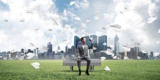 O homem de negócios no parque do verão que anuncia algo no altifalante e no papel aplana o voo ao redor Imagem de Stock Royalty Free