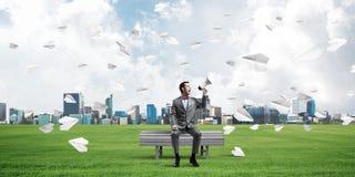 O homem de negócios no parque do verão que anuncia algo no altifalante e no papel aplana o voo ao redor Imagens de Stock Royalty Free
