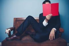 O homem de negócios no sofá está lendo Imagens de Stock Royalty Free