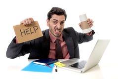 O homem de negócios no terno e o laço que senta-se na mesa de escritório que trabalha no portátil do computador que pedem a ajuda Fotos de Stock Royalty Free
