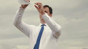 O homem de negócios no terno lança o brinquedo com o avião de papel do voo contra o fundo de nuvens escuras filme