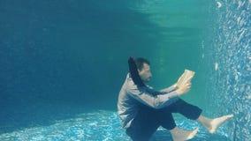 O homem de negócios no terno leu o livro sob a água filme
