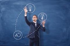 O homem de negócios nos ícones diáfanos brancos de manipulação do fundo azul do quadro que são conectados com o traço alinha Foto de Stock