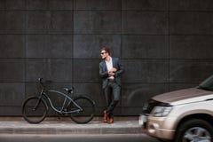 O homem de negócios novo à moda nos óculos de sol está perto de uma bicicleta Imagem de Stock