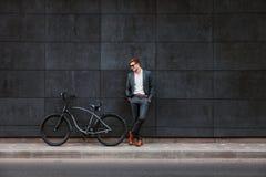 O homem de negócios novo à moda nos óculos de sol está perto de uma bicicleta Imagem de Stock Royalty Free