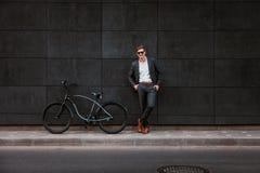 O homem de negócios novo à moda nos óculos de sol está perto de uma bicicleta Fotos de Stock Royalty Free