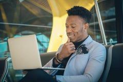 O homem de negócios novo é assentado no aeroporto que trabalha com um portátil imagem de stock royalty free