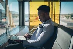 O homem de negócios novo é assentado no aeroporto que trabalha com um portátil foto de stock royalty free