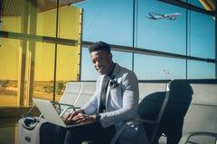 O homem de negócios novo é assentado no aeroporto que trabalha com um portátil foto de stock